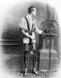 Young man wearing artificial legs and an artificial arm, 1890-1910.
