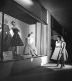 Two women looking at fashion display at night, Georgetown, Guyana, 1958.