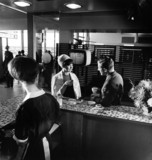 Cafeteria at Manchester Airport with waitres and couple having coffee, 1965