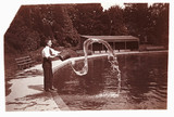 Man throwing a bucket of water into a pond, c 1905.