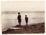 Two boys with hoops on the seashore, c 1905.