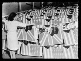 Factory worker laying out flags, 1945.