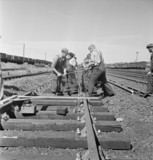 """Railway worker removing track, 1950."""