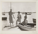 Three women getting out of a boat, c 1930.
