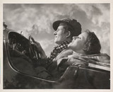 Couple in an open-top car, c 1930s.
