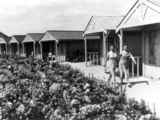 Two women walking past chalets at a Butlins holiday camp, 8 July 1939.