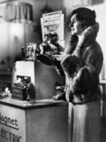 Woman beside a shop display of the latest Magnet electric iron, c 1930s.