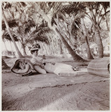 Woman lying beneath palm trees, c 1911.