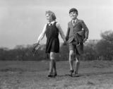 Boy and a girl wearing their school uniforms walking across a field, 1948