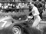 Stirling Moss walking away from his crashed BRM motor car, 1959.