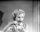 """Laughing little boy with a teddy bear, c 1950."""
