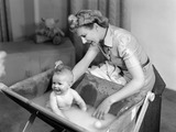 """Woman bathing a baby, 1948."""