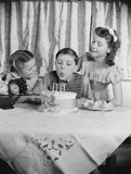 """Boy blowing out candles on a birthday cake, 1953."""