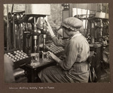 """'Woman drilling safety hole in fuses', 1915-1918."""