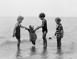 """Children playing in the sea, 1933."""