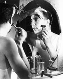 """Man shaving in front of a mirror, 1940s."""