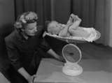 """Woman weighing a baby on a pair of scales, c 1949."""