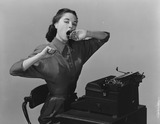 """Woman yawning at a typwriter, 1950."""