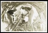 """Underground repairman and child cutting timber in a mine, 1931."""