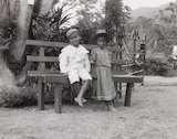 Two children sitting on a bench. Two children sitting on a bench in South America, c 1930s.