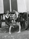 Couple in bathing costumes outside a beach hut, c 1910s.