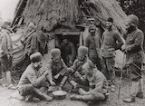 Algerian soldiers eating their national dish outside their hut in northern France, WWI.