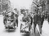 Wounded soldiers in wheelchairs carrying the Union Jack flag.