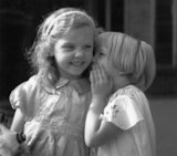 Small girl whispering into her friend's ear, c.1930s.