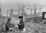 Two boys playing in front of a shipyard