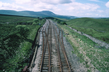 Two railway lines dividing into four, with hills in the distance.