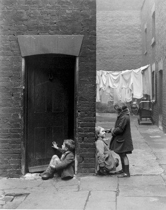Children playing outside their slum home in Southwark, 16 December 1932.