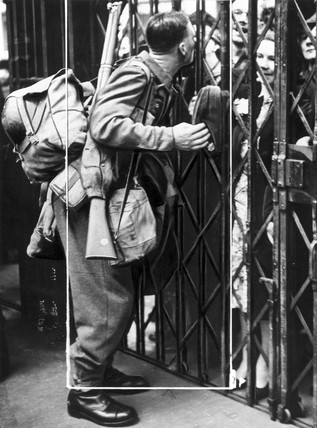 Soldier kising his wife through railings, Second World War, 15 May 1940.
