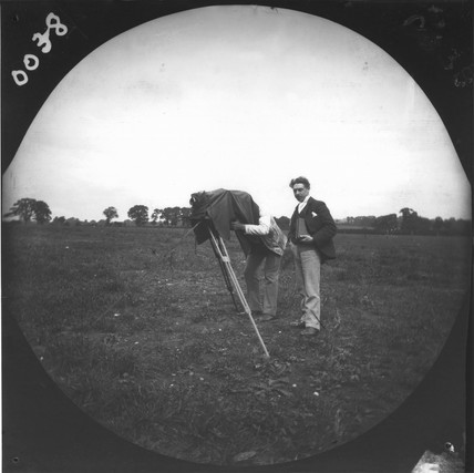 Two men in a field taking a photograph witha plate camera on a tripod, c 1890s.