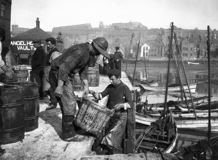 Fishermen unloading baskets of fish, Whitby, North Yorkshire, c 1900s.