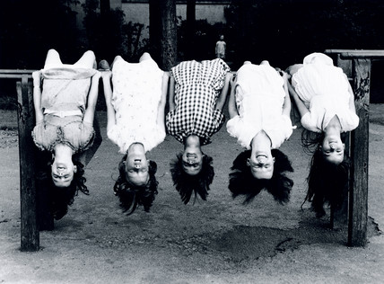 Five young girls hanging upside-down from a railing, c 1930s.