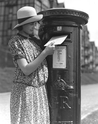 Young woman posting a letter, c 1930s.