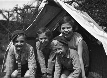 Four children smiling from the entrance of a tent, c 1920s.