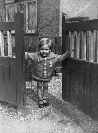 Small girl holding open the gate to her hou