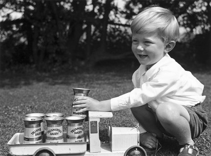 Small boy playing with a toy milk truck, c