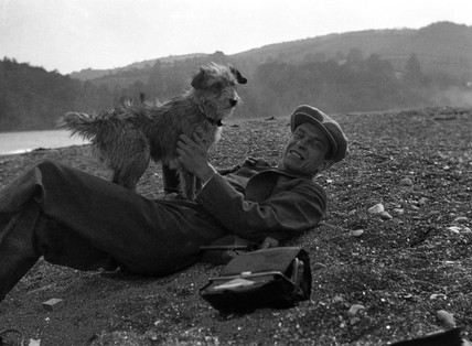 Man playing with a dog in the country, c 1930s.
