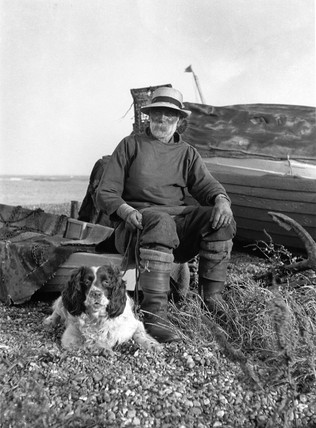 Fisherman and his dog next to a boat,  c 1910s.