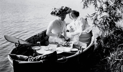 Enjoying a picnic in a rowing boat, c 1910s.