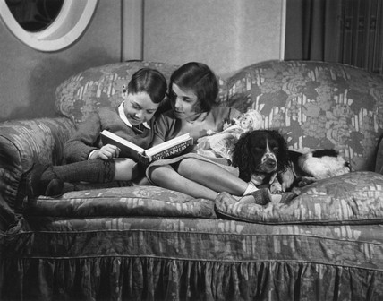 Two children on a settee reading 'Uncle Oojah's Big Annual', c 1930s.