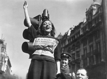 Young woman with a newspaper wrapped around