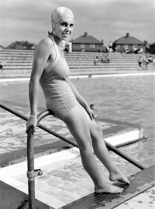 Woman wearing a bathing costume posing by a swimming pool, c 1920s.