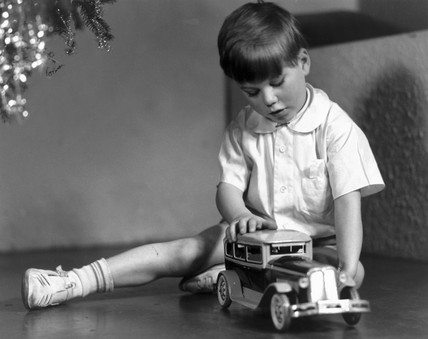 Boy playing with a toy car at Christmas, c