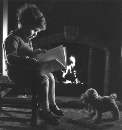 Small boy reading a book by a fireside, c 1930s.
