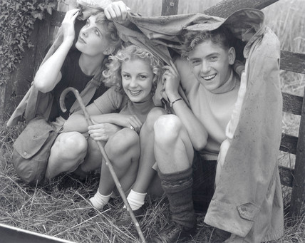 Three teenage ramblers sheltering from the rain, c 1945-1955.