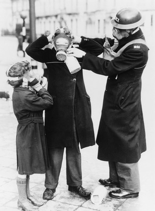 Policeman adjusting childrens' gas masks, Brighton, 17 February 1941.