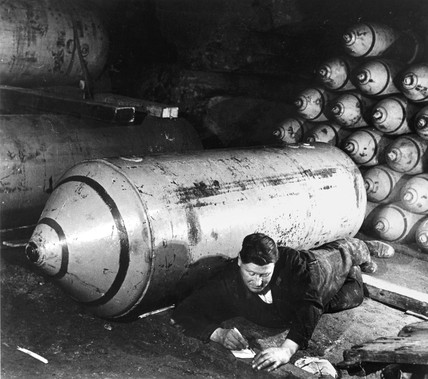 Man writing letter beside bomb, 12 November